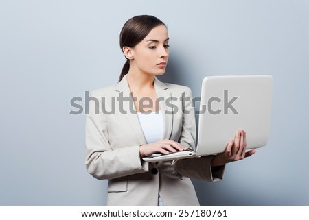 Busy with her work. Confident young businesswoman holding laptop while standing against grey background - stock photo