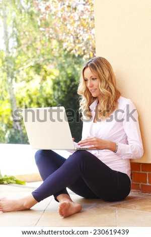 Busy woman sitting at garden and working on laptop.