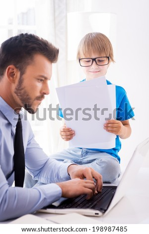 Busy working. Busy young man in shirt and tie working on laptop while his son in glasses sitting close to him and examining documents  - stock photo