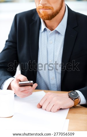 Busy working. Close-up of bearded businessman wearing watch and holding mobile phone while sitting at his working place - stock photo
