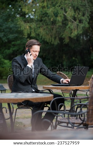 Busy working. Confident caucasian young man in formal wear working on laptop and talking on the mobile phone while sitting at the sidewalk cafe. - stock photo