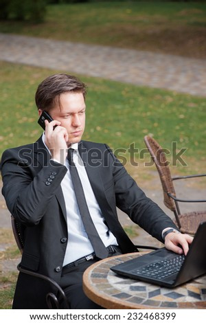 Busy working. Confident young man in formalwear working on laptop and talking on the mobile phone while sitting at the sidewalk cafe. - stock photo
