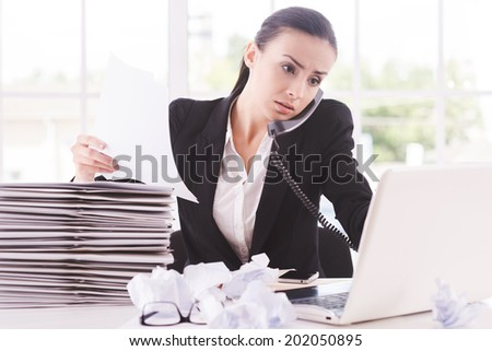 Busy working. Confident young woman in formalwear with documents and talking on the telephone while sitting at her working place - stock photo