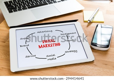 Busy working desk with tablet showing the information of digital marketing concept - stock photo