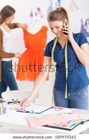 Busy working in design studio. Beautiful young female designer with measuring tape on shoulders talking on the mobile phone while her colleague standing on background  - stock photo