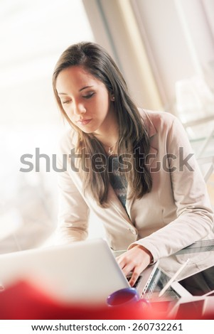 Busy young business woman working at desk typing on a laptop
