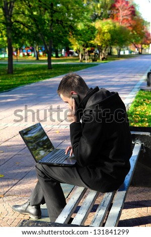 Busy Young man with Laptop sitting on the bench at the Autumn Park and Talking on Mobile Phone - stock photo