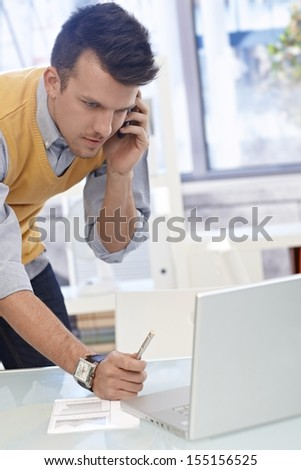 Busy young man working with computer, talking on mobilephone. - stock photo