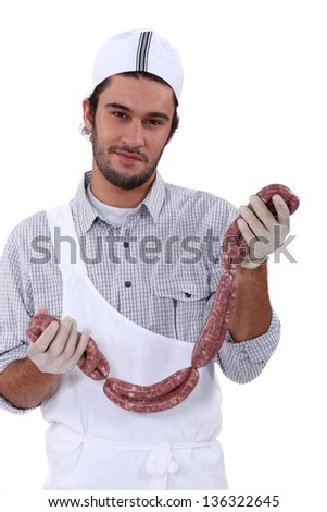 Butcher holding lots of sausages, - stock photo