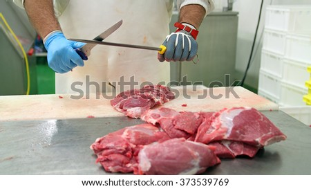 Butcher Sharpening Knife on Sharpening Steel.  Raw meat cuts on a table. Fresh raw pork chops in meat factory. Meat processing in food industry.  - stock photo