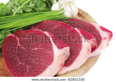 butchery : fresh raw beef lamb fillet ready to cooking with green stuff on wooden plate isolated over white background - stock photo