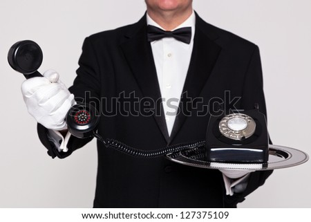 Butler handing you the receiver from a retro telephone upon a silver serving tray. - stock photo