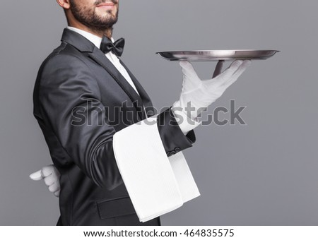 Butler holding a silver tray on gray background