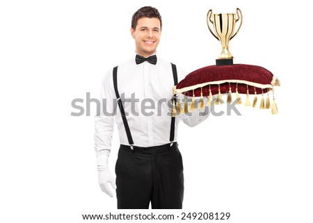 Butler holding a trophy on red pillow isolated on white background - stock photo