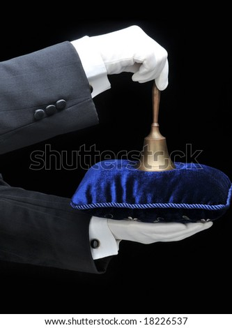 Butler holding a velvet pillow and a service bell - hands and arms only - stock photo