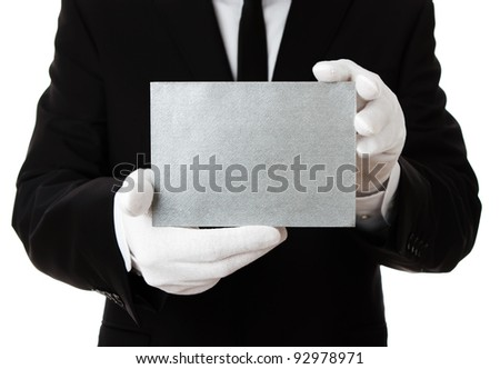 Butler holding blank silver invitation card with copy space - stock photo