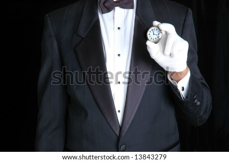 Butler in Tuxedo Holding a Pocket Watch with the Face pointing towards camera
