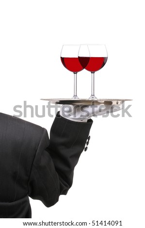 Butler in Tuxedo seen from behind with two red Wine Glasses on serving tray held at shoulder height vertical format over white - stock photo