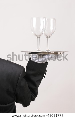 Butler in Tuxedo seen from behind with Wine Glasses on Tray held at shoulder height vertical format over gray - stock photo
