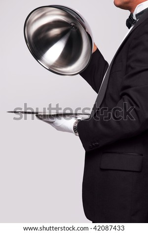 Butler lifting the cloche from a silver serving tray, insert your own object onto the tray. - stock photo