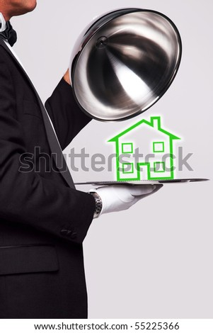 Butler lifting the cloche from a silver serving tray to reveal a house illustration, good image for housing themes. - stock photo