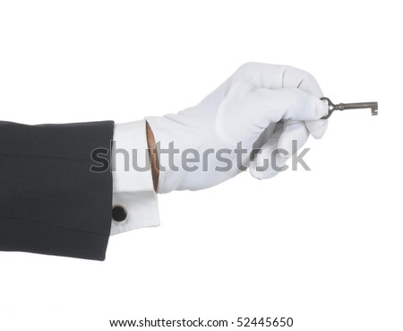 Butler's gloved hand holding an old key isolated over white. Hand and arm only in horizontal format. - stock photo