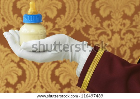 Butler's Hand with Bottle of Milk - stock photo