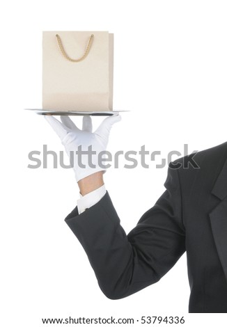 Butler wearing tuxedo and formal gloves holding a Gift Bag on a silver tray. Shoulder hand and arm only isolated on white vertical composition. - stock photo