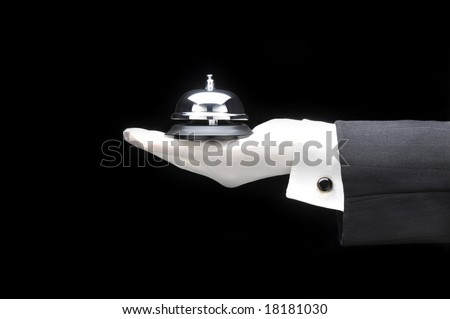 Butlers or concierge holding a service bell in his outstretched hand. Hand and arm only man is unrecognizable. - stock photo