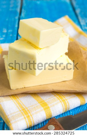 Butter and knife over blue rustic wooden table - stock photo