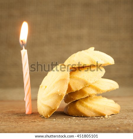 Butter and milk cookies placed stack on wooden table, selective focus with blurred background, with lighten candle on side - stock photo