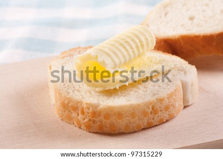 Butter curl on a slice of white bread (baguette, French bread) - stock photo