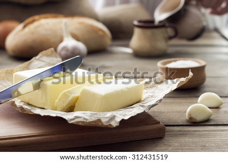 butter knife , bread , garlic and milk , breakfast in the countryside - stock photo