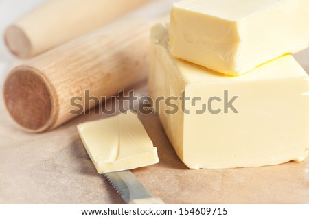 Butter on paper, kitchen utensil and knife - stock photo
