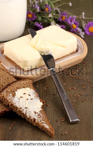 Butter on wooden holder surrounded by bread and milk on wooden table close-up