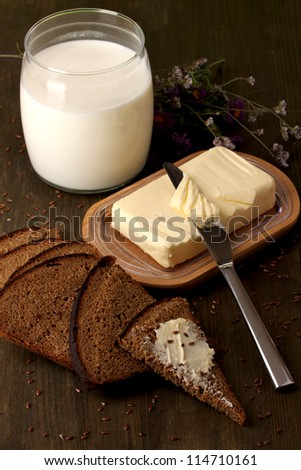 Butter on wooden holder surrounded by bread and milk on wooden table close-up - stock photo