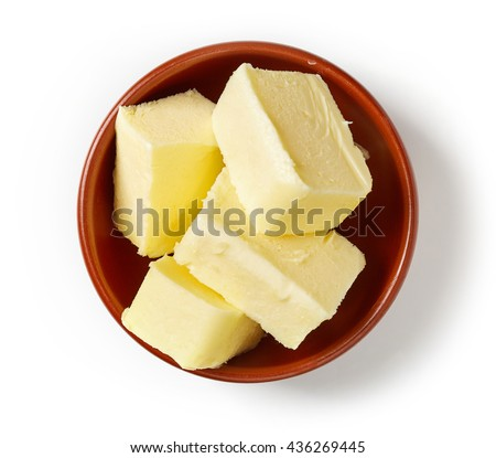 Butter pieces in clay bowl isolated on white background, top view - stock photo