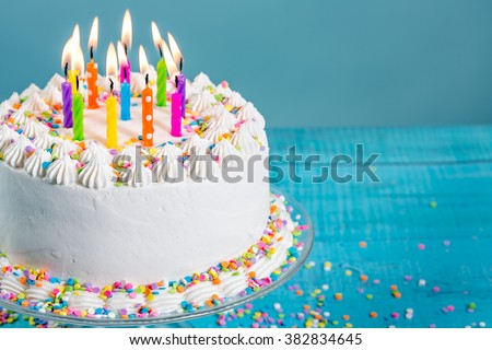 Buttercream birthday cake with colorful sprinkles and Candles over blue background - stock photo