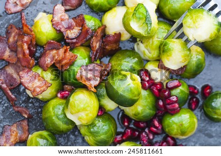 Buttered brussels sprouts with bacon and pomegranate. New version. - stock photo