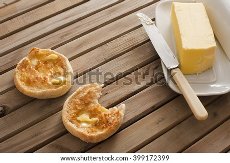 Buttered crumpets for breakfast with a pat of butter alongside on a plate served on a wooden table, one crumpet bitten into - stock photo
