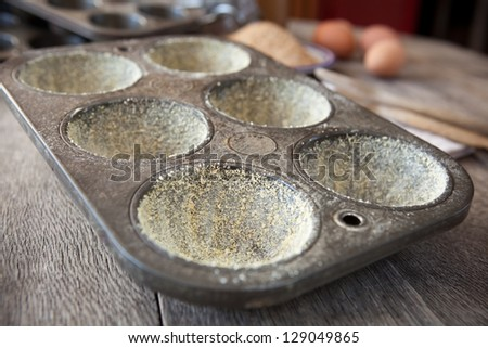 Buttered muffin tin with corn flour on table - stock photo