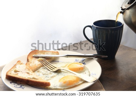 Buttered toast, fried eggs and coffee - stock photo