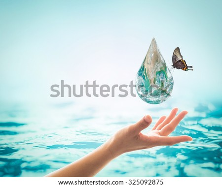 Butterfly drinking water from blue green globe droplets over female human hands with blurred water background: Saving clean environment protection/ campaign: Elements of this image furnished by NASA   - stock photo