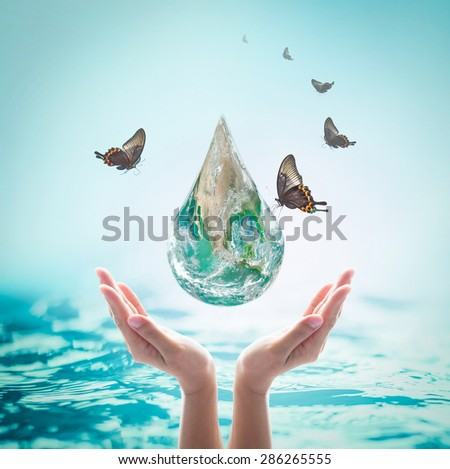 Butterfly drinking water from droplet shaped globe over supportive human hands on blurred turquoise color wavy water background: World environment concept: Elements of this image furnished by NASA  - stock photo