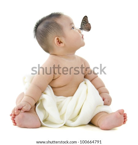 Butterfly flying to Asian baby boy nose, on white background - stock photo