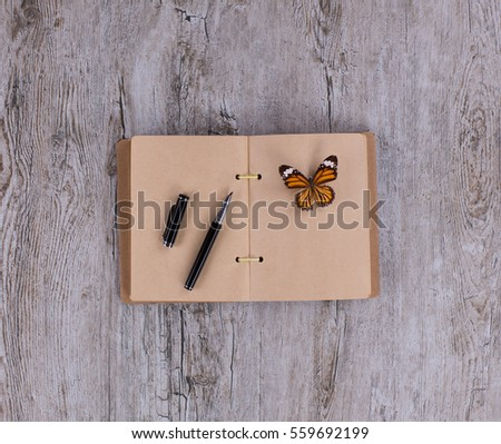 butterfly, notebook and pen, collector of butterflies, a wooden table