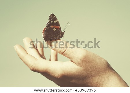 butterfly on the hand, peace concept, vintage retro style image
