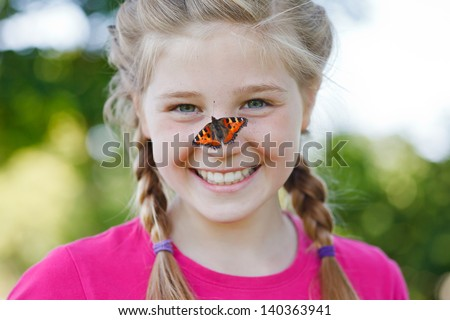 butterfly sitting on a girls nose - stock photo