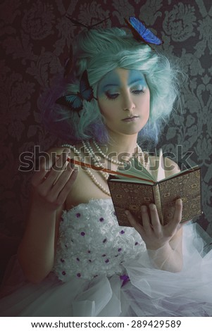 Butterfly woman reading a book - stock photo