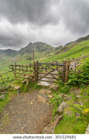 Buttermere looking towards the haystacks in the lake district cumbria through a gate - stock photo